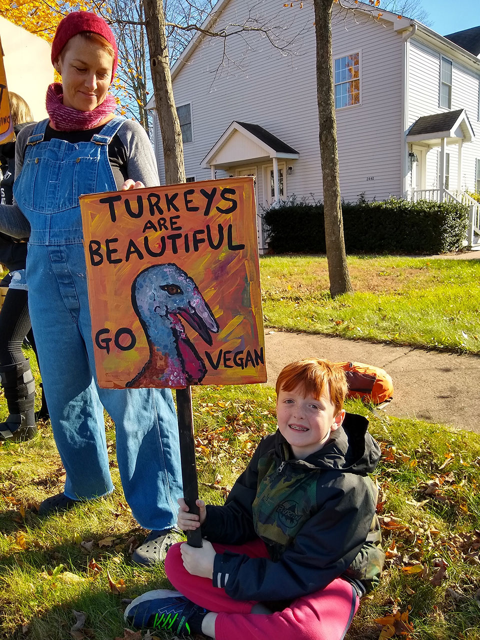 Protesters holding signs across the street from the Gozzi Turkey Farm.