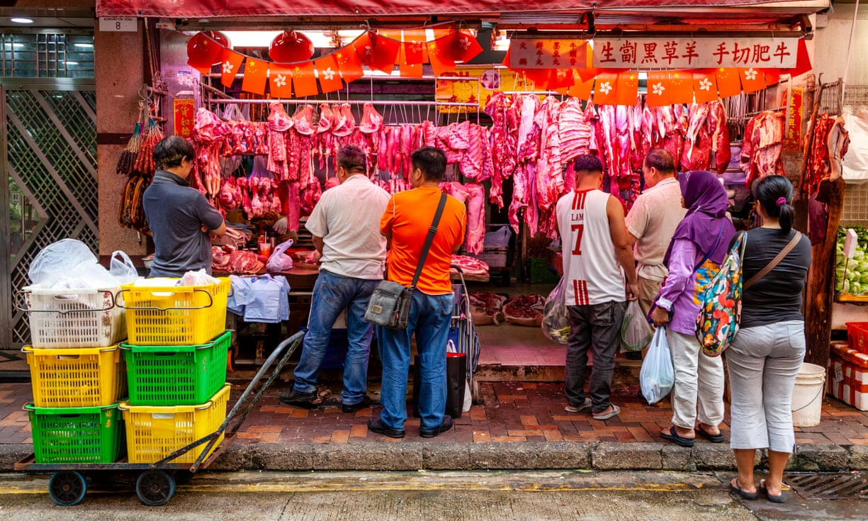 People buy meat at a butchers' shop at the Bowrington Road food market in Hong Kong.
