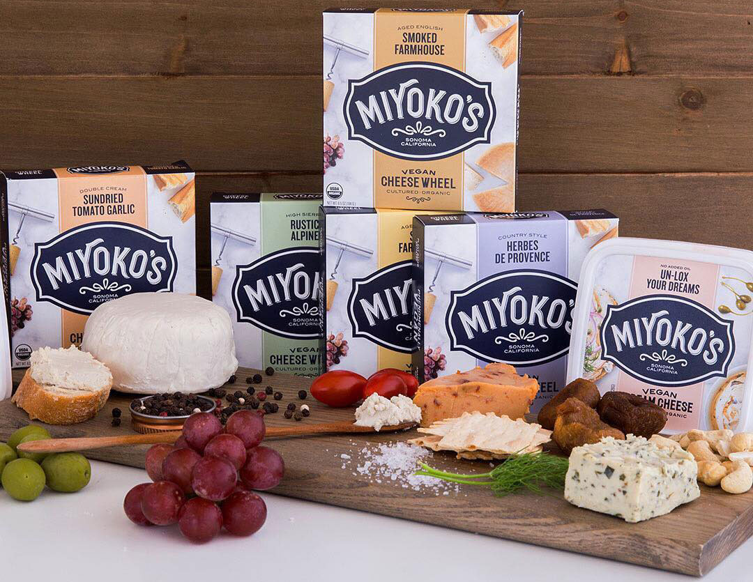 cutting board with crackers and various Miyoko cheeses
