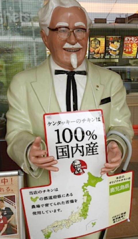 Life-size KFC Colonel statue holding Japanese sign