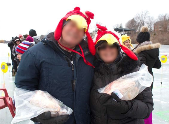 Couple standing on ice holding frozen chickens.