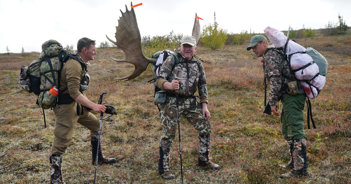 Hunters with walking sticks and wearing camouflage clothing