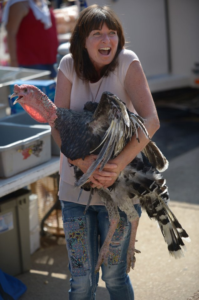 Woman laughing as she clutches a turkey