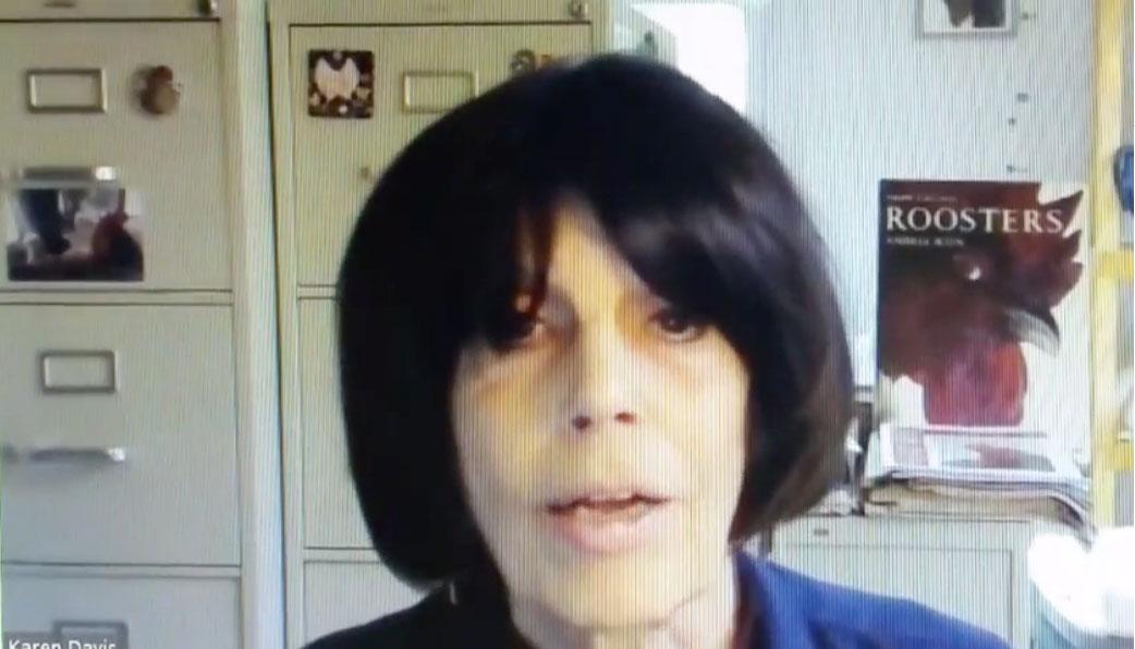 Karen at her desk being interviewed.